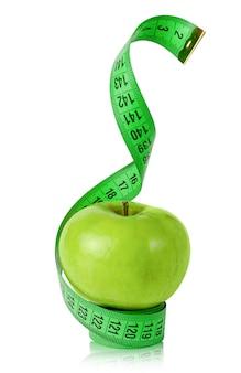 Manzana verde con cinta métrica aislada en blanco