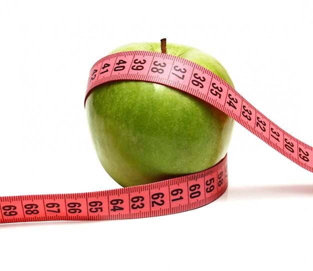 Manzana verde y cinta métrica para dieta