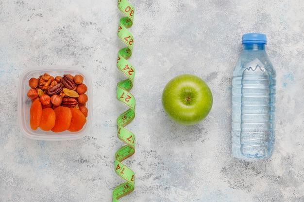 Manzana verde fresca, cinta métrica y botella de agua dulce sobre hormigón gris