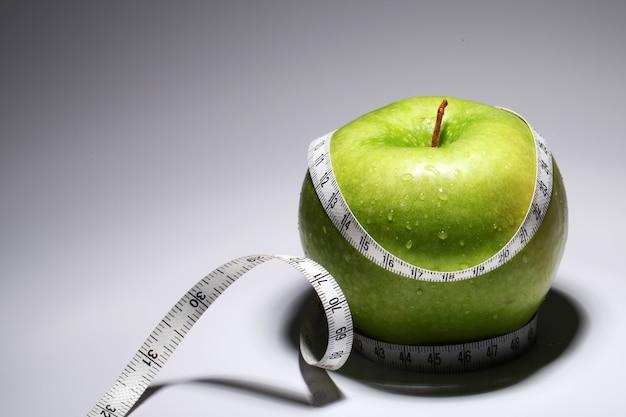 Manzana verde fresca con cinta métrica