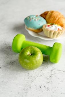 Manzana verde y mancuerna con alimentos dulces sobre fondo de hormigón
