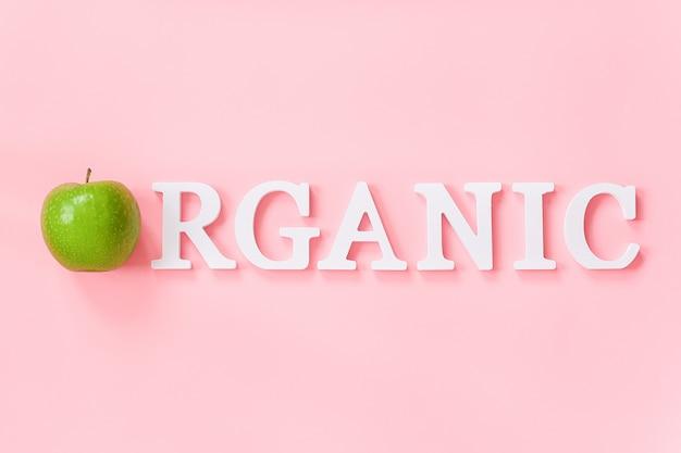 Manzana verde natural y texto orgánico de letras blancas de volumen. concepto creativo frutas orgánicas naturales alimentos