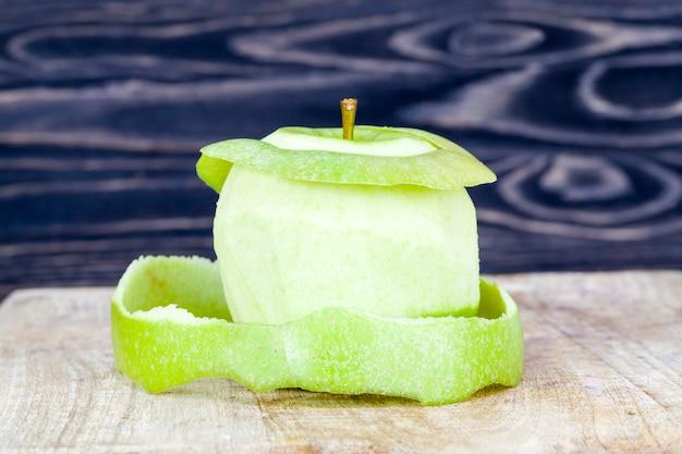 Manzana verde pelada sobre una tabla de cortar de madera, primer plano de alimentos de producción natural