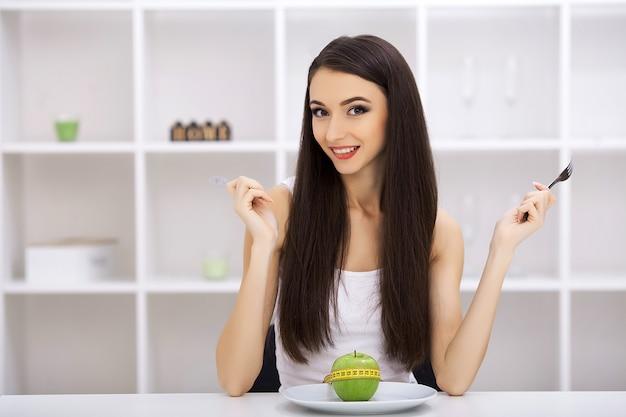Manzana verde en un plato blanco, tenedor, cuchillo, pérdida de peso, dieta saludable, cinta métrica amarilla, pérdida de peso