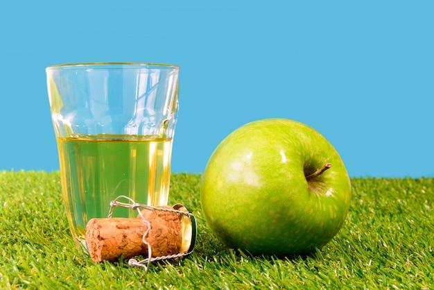 Una manzana verde con un vaso de sidra.