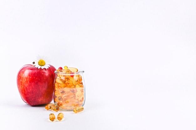Manzana y vitaminas en cápsulas copyspace. medicamentos y drogas para la salud.