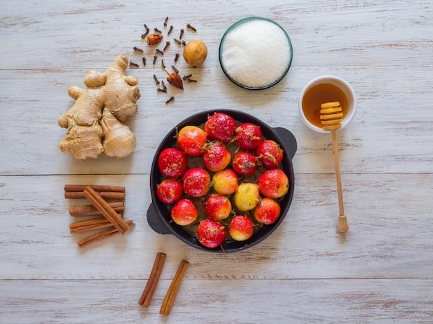 Manzanas al horno en una sartén con jengibre, canela, miel y pimienta en una madera.