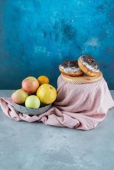 Manzanas amarillas aisladas sobre un mantel rosa.