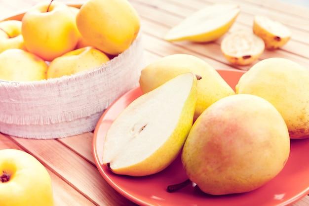 Manzanas amarillas, pera y guayaba cortadas por la mitad sobre una superficie de madera