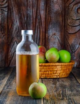 Manzanas con botella de bebida en una canasta sobre fondo de madera, vista lateral.