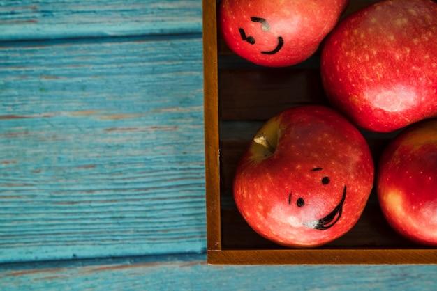 Manzanas con caras graciosas en caja de madera.