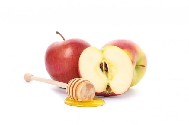 Manzanas y cazo con miel aislado en blanco