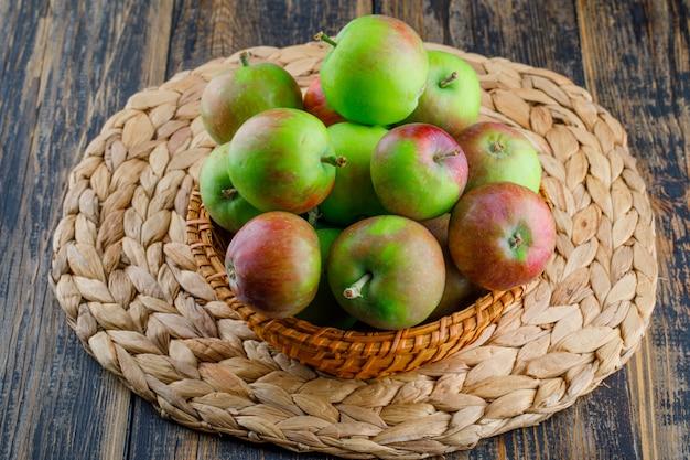 Manzanas en una cesta de mimbre sobre fondo de madera y mantel. vista de ángulo alto.