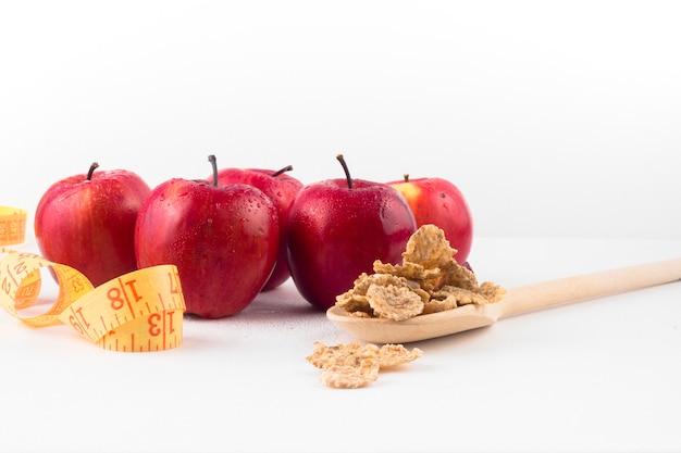 Manzanas con cinta métrica y cereales en cuchara.