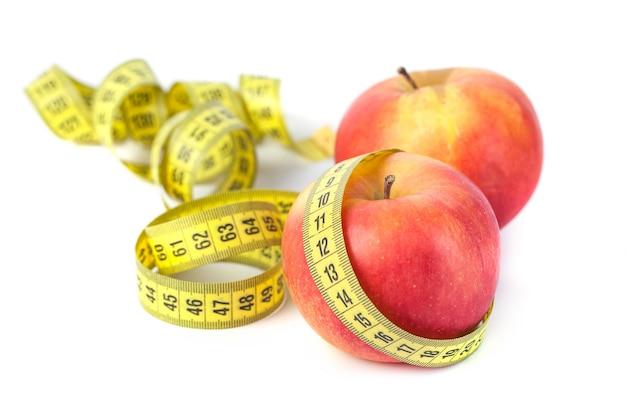 Manzanas con cinta métrica sobre fondo blanco, dieta saludable.