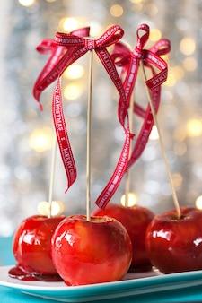 Manzanas confitadas caseras con un lazo rojo sobre un fondo de madera para navidad