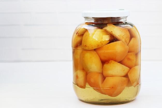 Las manzanas en conserva en almíbar en un frasco sobre un fondo blanco.