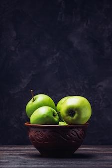 Manzanas con copia espacio sobre la mesa en un recipiente de arcilla
