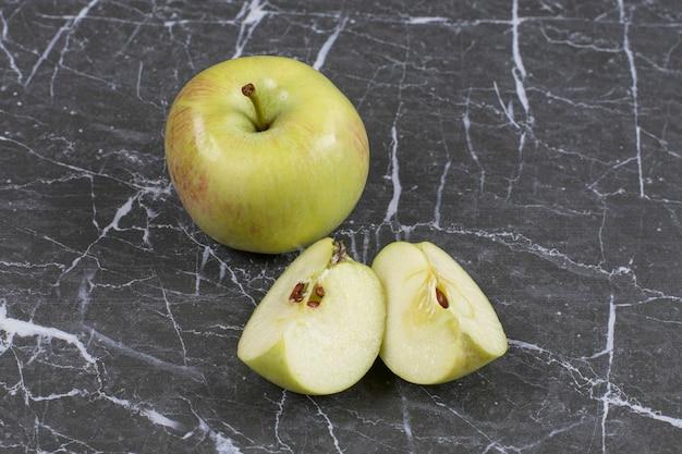 Manzanas enteras y en rodajas sobre mármol.