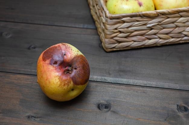 Manzanas feas en la cesta de mimbre en la mesa de madera marrón. de cerca.