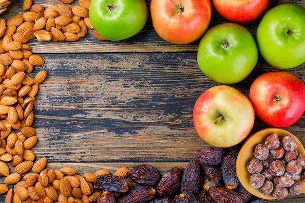 Manzanas con fechas, almendras y nueces en cuchara de madera sobre fondo de madera vieja, endecha plana.