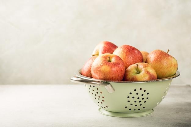 Manzanas frescas en colador de metal