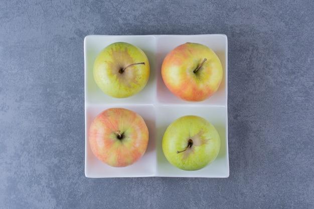 Manzanas frescas dulces en una mesa de mármol plateon.