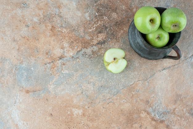 Manzanas frescas con una taza antigua sobre mesa de mármol.