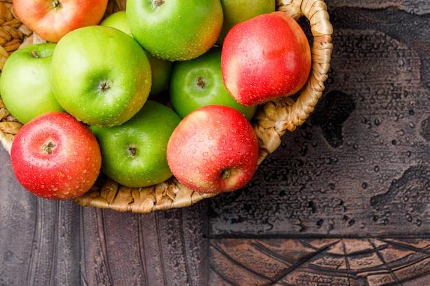 Manzanas frías en una cesta de mimbre sobre fondo de azulejos de piedra, endecha plana.