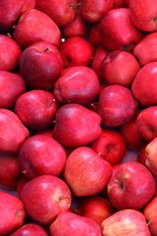 Manzanas frutos rojos maduros muchos apilados al azar.