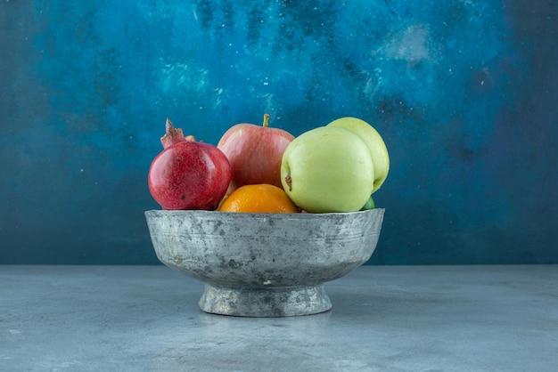 Manzanas, granadas y mandarinas en un cuenco de plata.