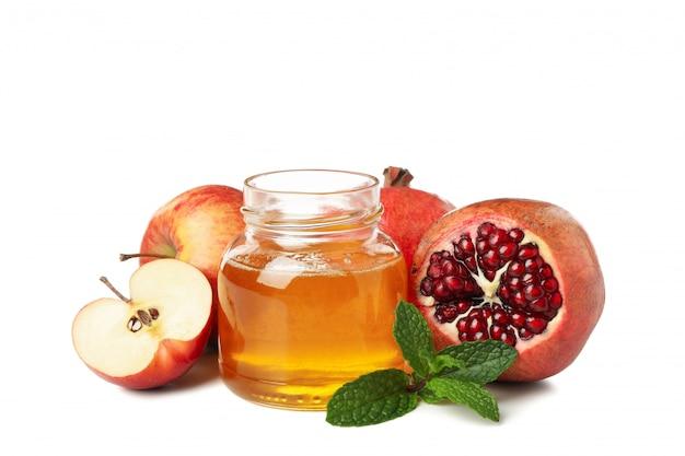 Manzanas, granadas y miel aislados en blanco. tratamiento natural