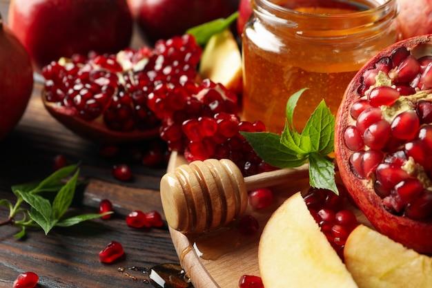 Manzanas, granadas y miel sobre madera, de cerca
