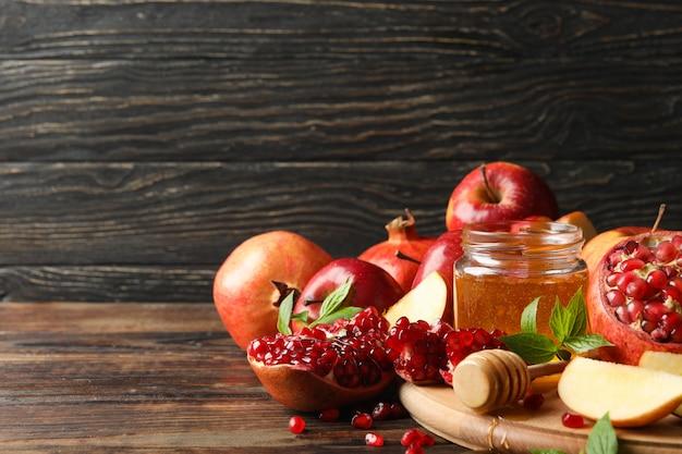 Manzanas, granadas y miel sobre madera, espacio para texto