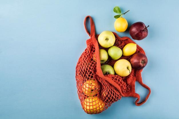 Manzanas y limones en una bolsa de cadena naranja sobre un fondo azul.