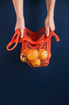 Manzanas y limones en una bolsa naranja en manos de hombres