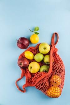 Manzanas y limones en una bolsa naranja