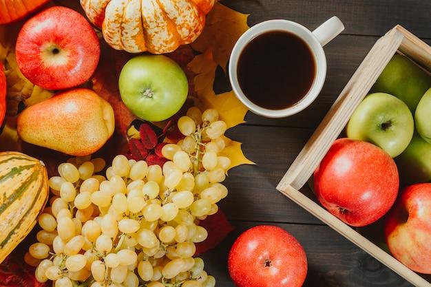 Manzanas maduras en una caja con calabazas, manzanas, uvas, peras y una taza de café en madera oscura.