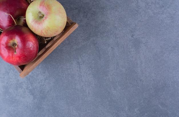 Manzanas maduras en caja sobre mesa de mármol.
