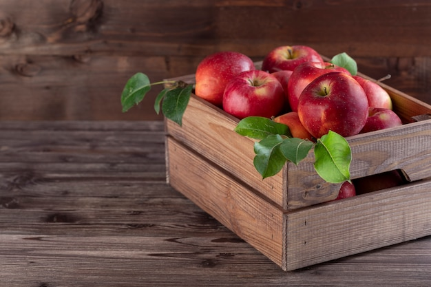 Manzanas maduras con hojas en cesta de madera sobre la mesa rústica.