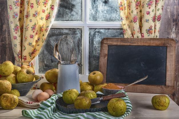 Manzanas orgánicas sobre la mesa con pizarra pequeña