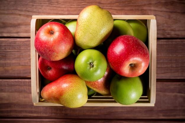 Manzanas y peras maduras en una caja de madera sobre fondo rústico de madera marrón oscuro