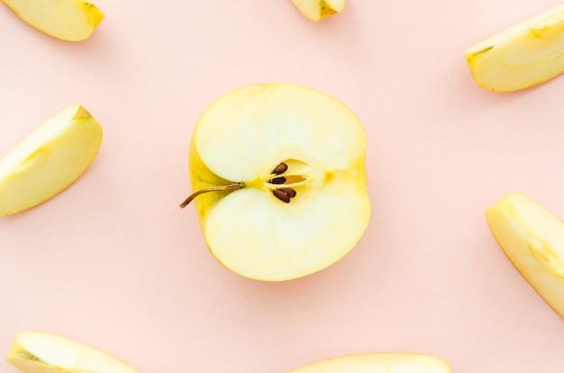 Manzanas picadas sobre fondo rosa pálido