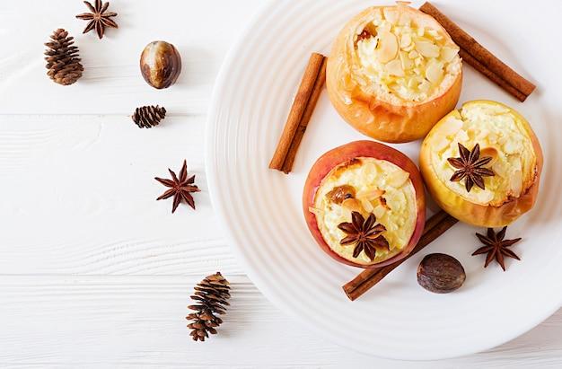 Manzanas rellenas al horno con queso cottage, pasas y almendras para navidad en una mesa blanca. postre de comida de navidad.
