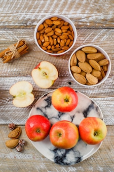 Manzanas y rodajas en un plato con palitos de canela, almendras peladas y sin pelar en tazones, nueces vista superior en madera