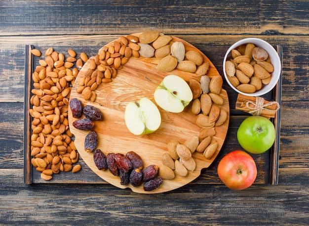 Manzanas y rodajas en una tabla de cortar con palitos de canela, fechas y almendras vista superior en pieza de madera y madera