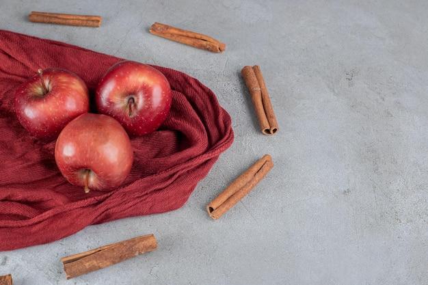 Manzanas rodeadas de cortes de canela sobre superficie de mármol.