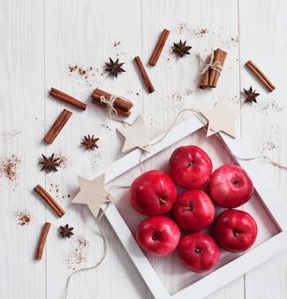 Manzanas rojas, canela y anice sobre fondo blanco de madera.