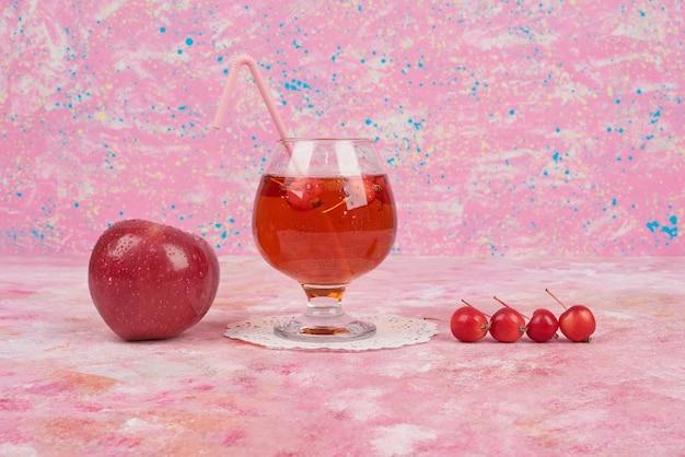 Manzanas rojas y cerezas con un vaso de jugo.