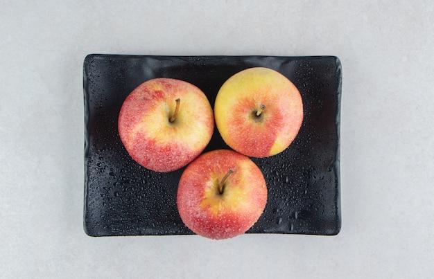 Manzanas rojas frescas en placa negra.